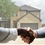 A Real Estate Agent and Homebuyer Shake Hands in Front of the Home for Sale in Rochester Hills, MI